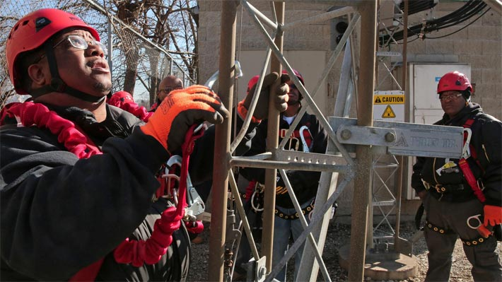 Antonio Crum, left, starts to climb while practicing maintenance work on a cell tower Feb. 27, 2016, in the 1400 block of South Ashland Avenue in Chicago. The men are in the inaugural class of the Safer Foundation's Wireless Field Engineer Training Program, which trains and places ex-offenders into cell tower technician jobs. (Anthony Souffle / Chicago Tribune)