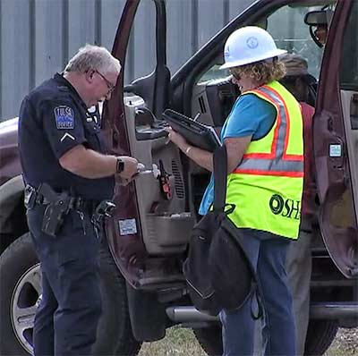 An OSHA inspector collects information from a Tulsa police officer. The fatality was the sixth industry death this year.