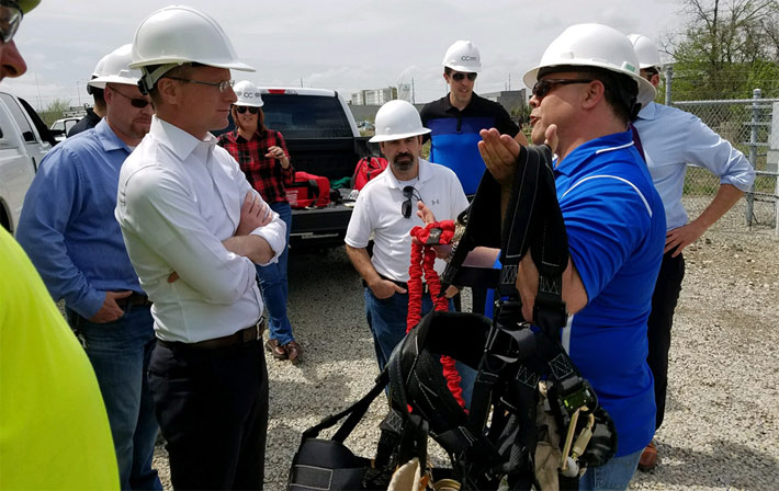 FCC Commissioner Brendan Carr, left, is being briefed on the exacting nature of tower tech installations and the required PPE from