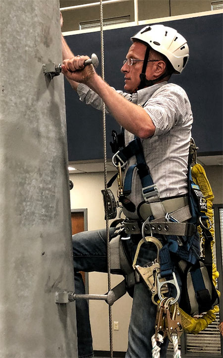 FCC Commissioner Brendan Carr practiced climbing on an indoor monopole at VIKOR Teleconstruction.
