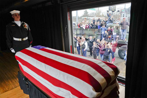 The flag-draped casket of former President George H.W. Bush passes through Magnolia, Tex., Thursday, along the route from Spring to College Station, Tex. (AP Photo/David J. Phillip, Pool)