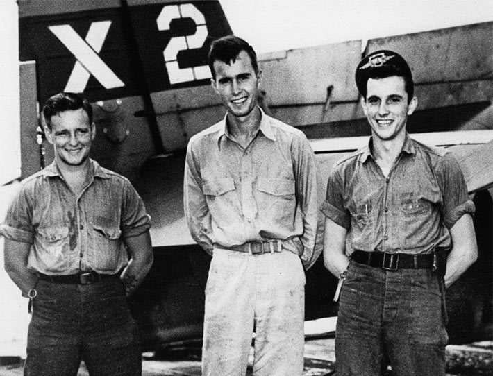 "A young George Bush, center, with Joe Reichert, left, and Leo Nadeau during World War II. Nadeau was Bush's gunner but was replaced on the mission by William ""Ted"" White who asked Bush to let him go on one bombing run to get the experience. White and radio operator John ""Del"" Delaney were killed after receiving anti-aircraft while they bombed a radio tower on a small island 700 miles south of Tokyo. (Robert B. Stinnett/National Archives)"