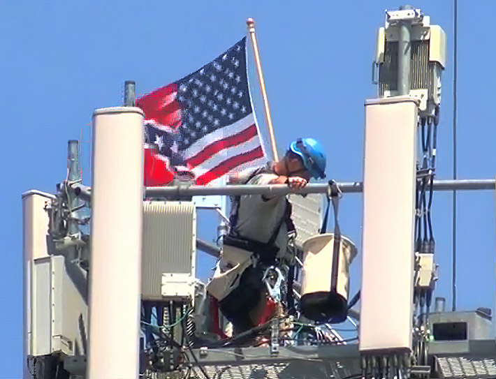 When the tower technician saw a TV reporter filming, he took down the flag. Photo: KMTV video frame capture