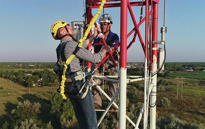 Federal Communications Commission Commissioner Brendan Carr, center, examines the installation of high-speed internet equipment Thursday on Midco's 330-foot telecommunications tower in Mitchell. Also pictured in the rear is Matt Hollingshead, of Midco. (Photo courtesy of Midco)